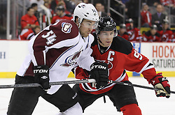 Mar 15; Newark, NJ, USA; New Jersey Devils left wing Zach Parise (9) and Colorado Avalanche right wing David Jones (54) battle for the loose puck during the second period at the Prudential Center.