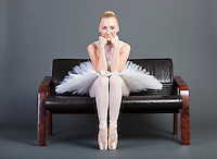 Portrait of young female ballet dancer sitting on sofa over grey background