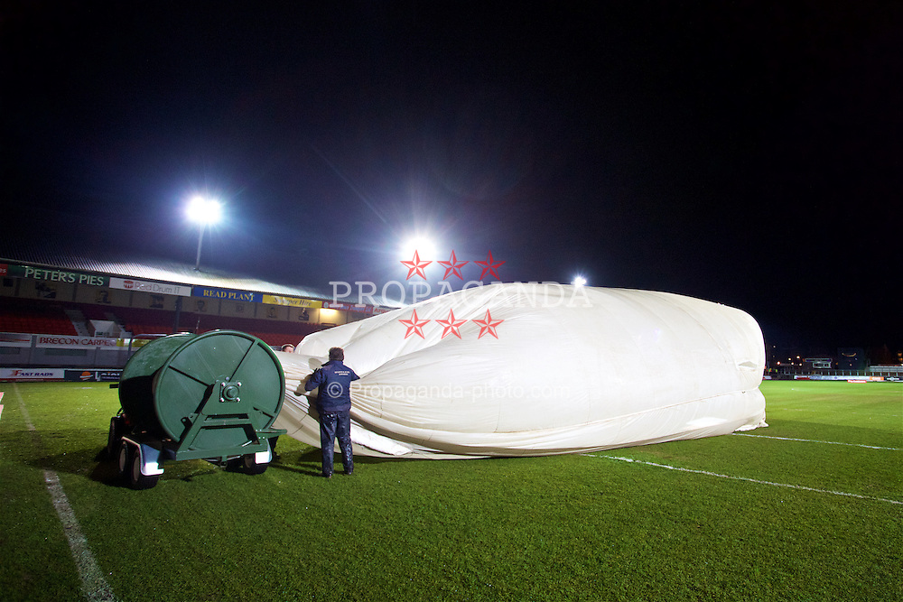 NEWPORT, WALES - Wednesday, December 21, 2016: Staff remove a large rain cover from the Rodney Parade pitch ahead of the FA Cup 2nd Round Replay between Newport County AFC and Plymouth Argyle. (Pic by David Rawcliffe/Propaganda)