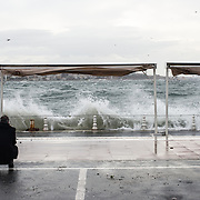 On a very windy day, a man takes photos of waves crashing into the wall on the Bosphorus Strait in Istanbul, Turkey.