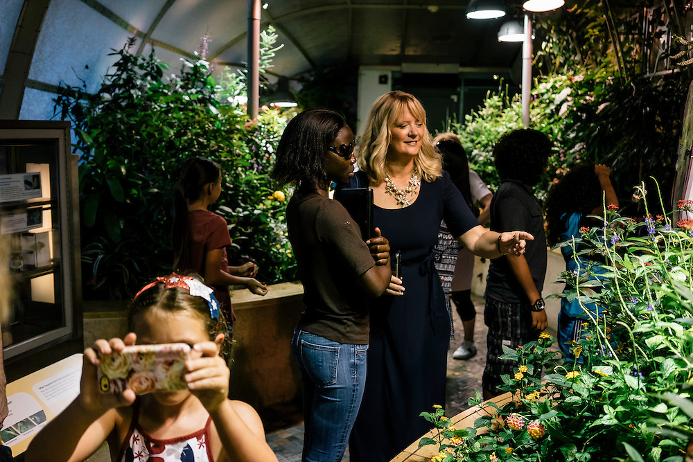 Lily, who escaped from Boko Haram during the kidnapping of almost 300 girls in Nigeria, tours the butterfly pavilion at the National Museum of Natural History in Washington, D.C. with Deanna Gelak, human development expert. Gelak is providing Lily and other girls who escaped, a summer of english and enrichment programs.
