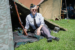 A female re-enactor portrays a Wehrmacht Heferin with the German Army in work uniform blouse shelters from the sun in the shade of a Zeltbahn. Wehrmacht Heferinnen were he German Armed Forces female Auxiliaries. At various periods of time during world war two they were sometimes classified as military personnel other times as uniformed civilians employed by the German Armed Forces (Wehrmacht)<br />