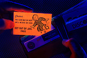 "A hand pulls a glowing ""Get Out Of Jail Free"" card from a wallet.Black light"