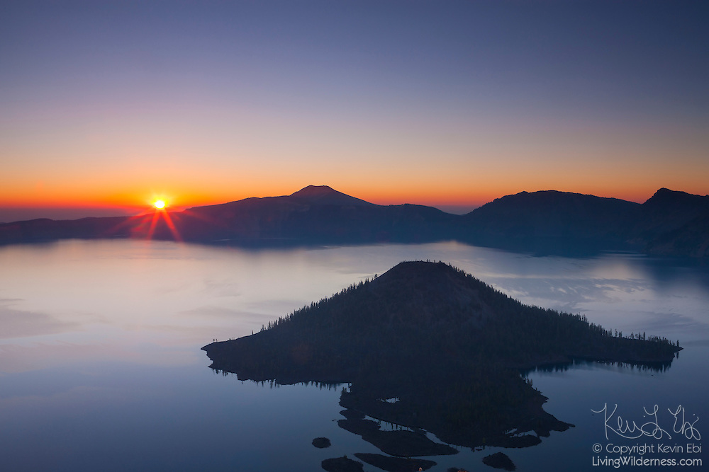 The rising sun clears the eastern caldera rim of Crater Lake, Oregon. Wizard Island, a dormant volcanic cone formed after the cataclysmic eruption of the ancient Mount Mazama, is visible in the foreground. Crater Lake, protected as a national park, is the deepest freshwater lake in North America.