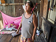 01 JULY 2015 - THA CHAI, CHAI NAT, THAILAND: UNCHALEE, a woman who lives along the Chao Phraya River in Chai Nat province looks around her home, most of which slid into the river after the land under the home collapsed because of drought. Central Thailand is contending with drought. By one estimate, about 80 percent of Thailand's agricultural land is in drought like conditions and farmers have been told to stop planting new acreage of rice, the area's principal cash crop. Water in reservoirs are below 10 percent of their capacity, a record low. Water in some reservoirs is so low, water no longer flows through the slipways and instead has to be pumped out of the reservoir into irrigation canals. Farmers who have planted their rice crops are pumping water out of the irrigation canals in effort to save their crops. Homes have collapsed in some communities on the Chao Phraya River, the main water source for central Thailand, because water levels are so low the now exposed embankment is collapsing. This is normally the start of the rainy season, but so far there hasn't been any significant rain.     PHOTO BY JACK KURTZ