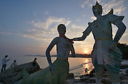Hat Sai Kaew. Mermaid and traditional Thai statues. Tourists watching sunset.