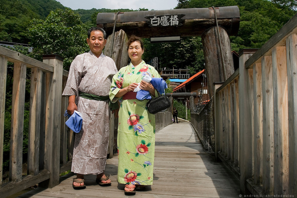 Old Japanese couple wearing yukata on the bridge over Takaragawa river, on the way to the hot springs of the Takaragawa onsen (hot spring), in Gunma prefecture north of Tokyo - JAPAN 8 July 2006