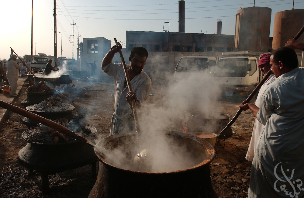 Iraqi Shia Muslim men prepare giant vats of rice and sauce to feed the poor near the Khadimiya shrine September 22, 2003 in Baghdad, Iraq to mark the anniversary of the death of the Imam Moussa Kadhim.  Khadim, a revered Shiite imam was poisoned some 900 years ago, and to this day Shia Muslims mark the date of his death with marches, self flagellation, prayers, and acts of charity for the poor.