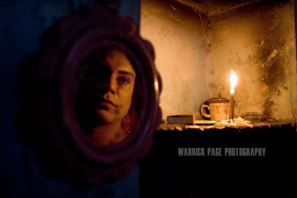 """LAHORE, PAKISTAN - DECEMBER 12: A Hijras (eunuch) looks at his refection by candlelight in his small apartment, December 12, 2006, Lahore, Pakistan. The suspected hideout of Osama Bin Laden, Al Qaeda leaders and countless Islamic militants, Pakistan is also home to one of the subcontinents largest communities of transsexuals, eunuchs and transvestites, or as they are more commonly known - Hijras. Caught between modernity and fundamentalism at the frontline in the war against terror, the Islamic Republic is a country at war with its own identity, yet its Kushras (Urdu for eunuch) stand out as a tight-nit community of devout Muslims. As Pakistan's most marginalised community, they live in fear """"24 hours a day"""", according to the group She-male Rights of Pakistan. Hijras are considered by many as unclean, amoral, drug users, and who also have the ability to place curses. (Photo by Warrick Page)"""