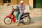 08 MARCH 2006 - A woman uses her cell phone whille her daughter gets ready to ride with her mom, in Ho Chi Minh City (formerly Saigon). Photo by Jack Kurtz / ZUMA Press