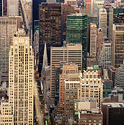 "New York City has endless opportunities for compositions to photograph.  This frame contained our dense metropolis in action.  Fifth avenue cuts diagonally down the frame with the cars racing by.  A tiny snippet of Fall leaves can be noticed in the upper left corner.  The shapes and geometry of the buildings is dizzying yet full of interest.  And then there are those rich beautiful colors, which are attributable to the film that I used.  This photograph is presented in a limited edition of 75 prints at 48""x48,"" 50 in sectionals aggregating 60""x60,"" and 25 in sectionals aggregating 72""x72."" Smaller sizes are available upon request as an open edition."