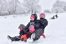 © Licensed to London News Pictures. 10/12/2017. London, UK. A family enjoys sledding on a snow covered golf course as snow falls in Northwood, north west London.  The weather forecast predicts an accumulation of three to four inches with snow continuing to fall well into the afternoon.  Photo credit: Stephen Chung/LNP