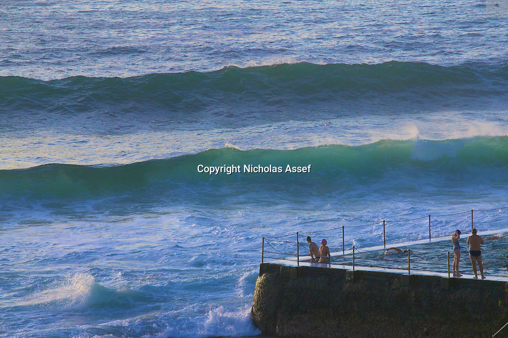 Waves line up to crash into Bondi Icebergs as swimmers enjoy a morning dip on a hot Summer morning
