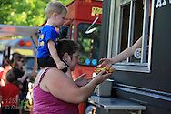 Mom buys french fries with son on shoulders on a summer evening in Jefferson Barracks Park during one of the many Food Truck Fest events sponsored throughout summer by St. Louis County Parks; St. Louis, MO