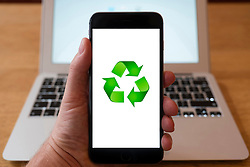 Using iPhone smartphone to display logo of standard symbol for recycling