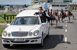 © Licensed to London News Pictures. 21/08/2018. Epsom, UK. A family member sits in the window of a hearse carrying the coffin of traveller Mikey Connors as it races along a road on Epsom Downs before his burial at a nearby cemetery. 32 year-old Mikey Connors, the nephew of My Big Fat Gypsy Wedding star Paddy Doherty, was killed when his horse-and-cart was hit by a car in Thamesmead on July 28. Photo credit: Peter Macdiarmid/LNP