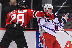 Jan 31; Newark, NJ, USA; New Jersey Devils defenseman Anton Volchenkov (28) hits New York Rangers left wing Brandon Dubinsky (17) during the third period at the Prudential Center.  The Devils defeated the Rangers 4-3 in an OT shootout.