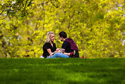 London, April 25th 2015. Despite the threat of forecasted showers, spring sunshine and warmth greets Londoners as they enjoy the Royal Parks in the capital. PICTURED: Spring sunshine and blossoming romance as Londoners Victoria Askey and Iain Killoughery enjoy a picnic in Green Park.
