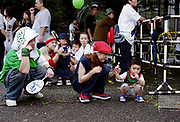 Family of B-boys and B-girls posing and sucking lollipops, Japan, 2003
