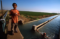 TURKEY HARRAN JUL02 - Boys play in an irrigation canal diverting water from a tributary to the Euphrates river in the Syrian plain. Without irrigation from the a tributary to the Euphrates river, the entire area would revert to arid wasteland...jre/Photo by Jiri Rezac..© Jiri Rezac 2002..Contact: +44 (0) 7050 110 417.Mobile:  +44 (0) 7801 337 683.Office:  +44 (0) 20 8968 9635..Email:   jiri@jirirezac.com.Web:     www.jirirezac.com