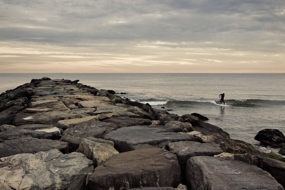 A surfer catches a wave near a jetty at dusk in Rockaway Beach, Queens, NY.