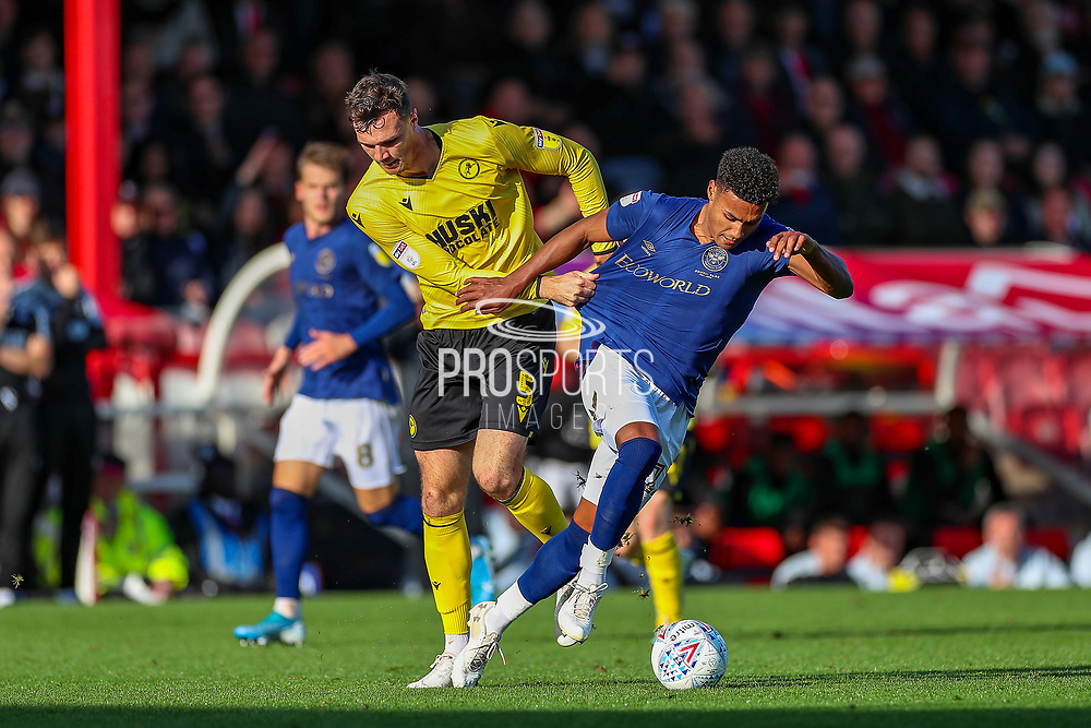 Brentford forward Ollie Watkins (11) tangles with Millwall defender Jake Cooper (5) during the EFL Sky Bet Championship match between Brentford and Millwall at Griffin Park, London, England on 19 October 2019.
