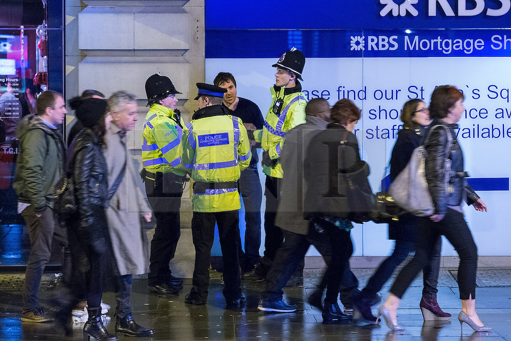 """© Licensed to London News Pictures . 19/12/2014 . Manchester , UK . Police handcuff and detain a man outside TGI Fridays in Manchester City Centre . """" Mad Friday """" revellers out in the rain and cold in Manchester . Mad Friday is typically the busiest day of the year for emergency services , taking place on the last Friday before Christmas when office Christmas parties and Christmas revellers enjoy a night out .  Photo credit : Joel Goodman/LNP"""