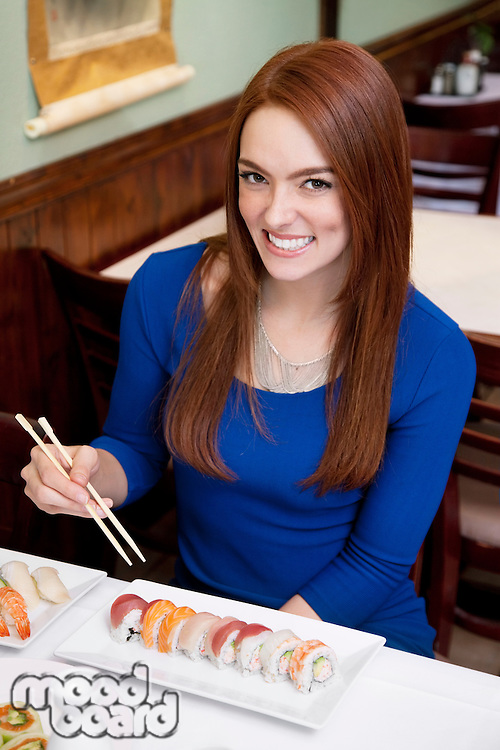 Portrait of a happy young woman eating sushi in Japanese restaurant