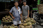 Tan Eow Chong (left) and his protege son Tan Chee Keat stand for a photo surrounded by durians in Durian Kaki, Tan Eow Chong's roadside durian stall, in Bayan Lepas, Pulau Pinang, Malaysia on June 17th, 2019. Tan Eow Chong is an award-winning durian farmer famed for his Musang King variety, and last year exported 1000 tons of the fruit to China from his family-run durian empire, expanding from an 80 acre farm to 1000 acres.  Photo by Suzanne Lee/PANOS for Los Angeles Times