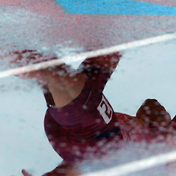 A relay runner is reflected in a puddle during the Arcadia Invitational at Arcadia High School in Arcadia, Calif., on Saturday, April 9, 2016.
