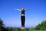 healthy young woman jumping with joy
