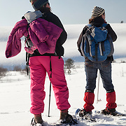 Two woman on snowshoes looking at a scenery with snow