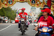 "10 DECEMBER 2012 - BANGKOK, THAILAND:  A Red Shirt protestor rides his motorcycle on Ratchadamnoen Avenue in Bangkok Monday. The Thai government announced on Monday, which is Constitution Day in Thailand, that will speed up its campaign to write a new charter. December 10 marks passage of the first permanent constitution in 1932 and Thailand's transition from an absolute monarchy to a constitutional monarchy. Several thousand ""Red Shirts,"" supporters of ousted and exiled Prime Minister Thaksin Shinawatra, motorcaded through the city, stopping at government offices and the offices of the Pheu Thai ruling party to present demands for a new charter.        PHOTO BY JACK KURTZ"