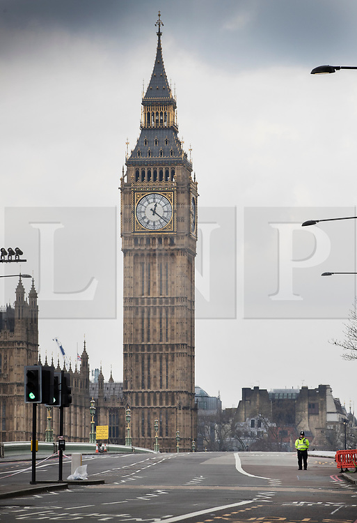 © Licensed to London News Pictures.23/03/2017.London, UK. A policeman stands alone on Westminster Bridge as it is readied to be re-opened the day after a lone terrorist killed 4 people and injured several more, in an attack using a car and a knife. The attacker managed to gain entry to the grounds of the Houses of Parliament, killing one police officer.Photo credit: Peter Macdiarmid/LNP