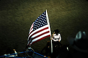 USA flag parade by female cowboy during a rodeo event
