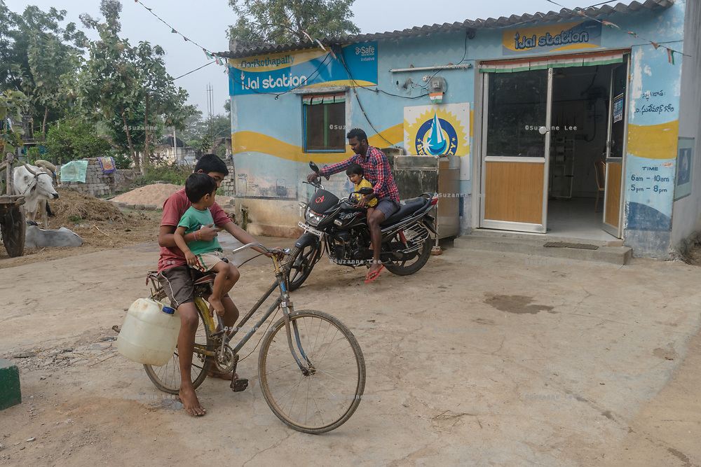 People carry plastic can of water at a Safe Water Network iJal station in village Gorikothapally, Telangana, Indiia, on Friday, February 8, 2019. Photographer: Suzanne Lee for Safe Water Network