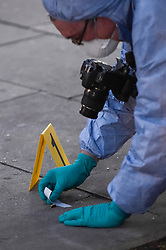 © Licensed to London News Pictures. 21/08/2018. LONDON, UK. A forensics officer examines a bullet casing next to an evidence marker. A police cordon is set up on Imperial Drive near Rayners Lane tube station, north west London, following a shooting in which two men suffered gunshot wounds.  It is reported that the suspect and accomplice have been.   Investigations are ongoing.  Photo credit: Stephen Chung/LNP