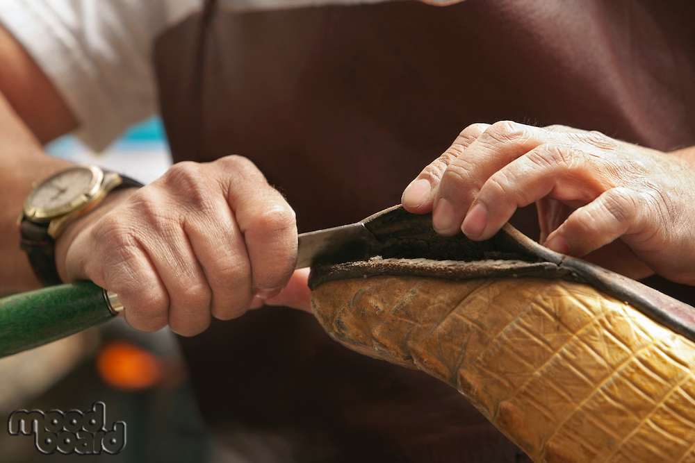Cropped image of shoemaker cutting edge of sole