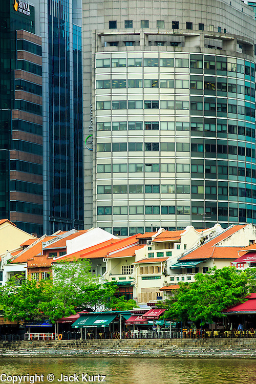 18 DECEMBER 2012 - SINGAPORE, SINGAPORE: Modern high rise office and bank buildings rise over traditional shophouses converted into trendy bar and restaurants on the Boat Quay (Key) along the Singapore River waterfront. PHOTO BY JACK KURTZ
