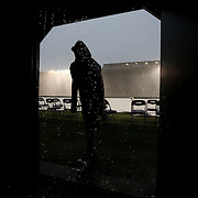 A fan waits for the rain to stop during the game at Harvard Stadium on May 10, 2014 in Boston, Massachusetts. (Photo by Elan Kawesch)