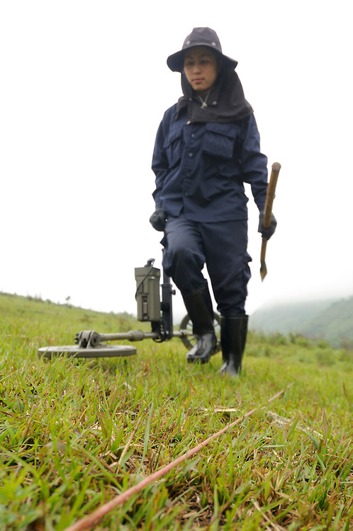 "Mines Advisory Group, Technician, Sia Thorthongyer, age 19, uses a metal detector to uncover live bombs hidden in the soil.  Sia and her partner Vonekham said, ""The first time we found a bomb we were afraid.  But we have good training and team work.  We have found many bombs, now it is just normal.  But, if we see a snake - we drop everything and run!"" ..Laos was part of a ""Secret War"", waged within its borders primarily by the USA and North Vietnam.  Many left over weapons supplied by China and Russia continue to kill.  However, between 90 and 270 million fist size cluster bombs were dropped on Laos by the USA, with a failure rate up to 30%.  Millions of live cluster bombs still contaminate large areas of Laos causing death and injury.  The US Military dropped approximately 2 million tons of bombs on Laos making it, per capita, the most heavily bombed country in the world.   ..The women of Mines Advisory Group (MAG) work everyday under dangerous conditions removing unexploded ordinance (UXO) from fields and villages...***All photographs of MAG's work must include (either on the photo or right next to it) the credit as follows:  Mine clearance by MAG (Reg. charity)***."