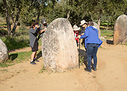 Tourists inspecting the standing stones looking for feint carved markings, Neolothic stone circle of granite boulders, Cromeleque dos Almendres, Evora district, Alentejo, Portugal, southern Europe