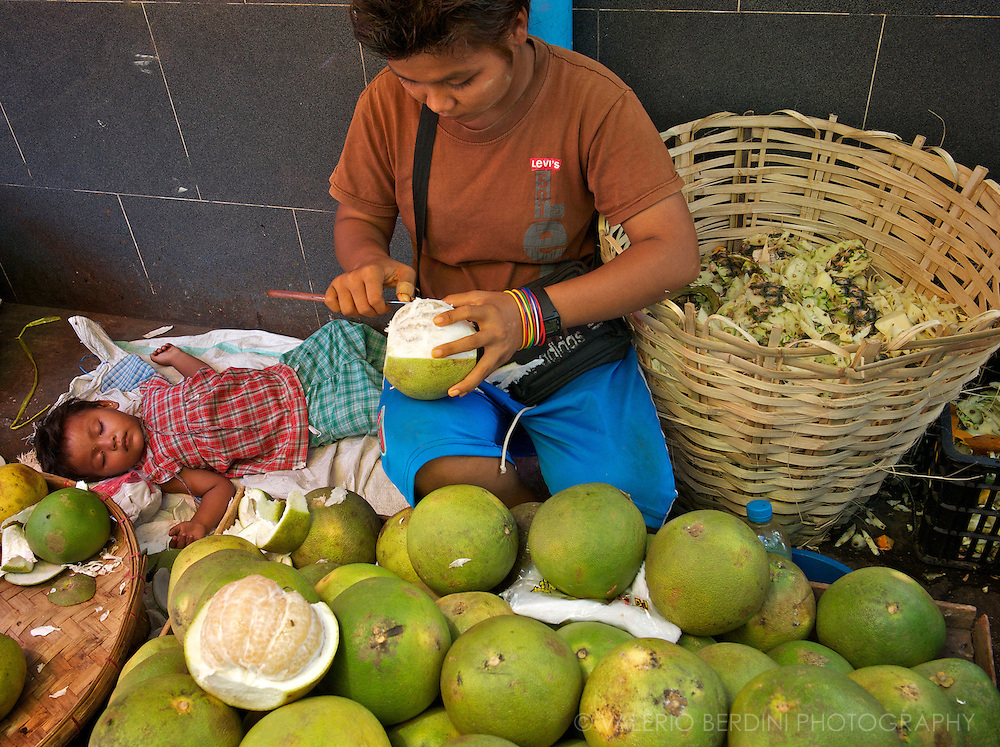 A mother and her sleeping baby selling pomelos on a street of Rangoon. The large green citrus is a variety of grapefruit common in Southeast Asia.