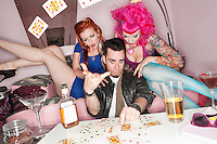 Man tossing playing cards in air with women sitting besides him