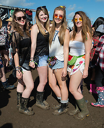 © Licensed to London News Pictures. 28/08/2015. Reading Festival, UK. Festival goers at Reading Festival on Day 1 of the festival, pose in wellington boots in the mud, minutes before the dates to the arena are due to open for the first timePhoto credit: Richard Isaac/LNP