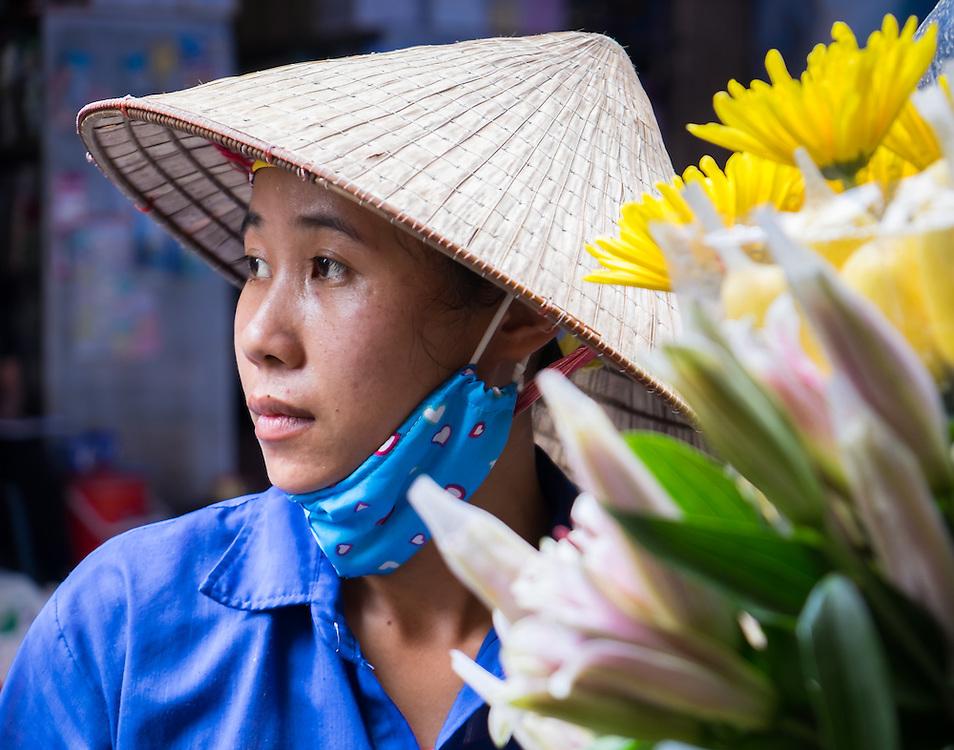 HANOI, VIETNAM - CIRCA SEPTEMBER 2014:  Portrait of Vietnamese woman selling flowers in the streets of Hanoi, Vietnam.