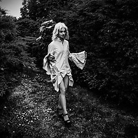 Young blonde female model wearing only a blouse with flared sleeves walking.