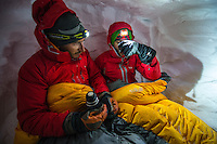 A male mountaineer covered with a sleeping bag drinks a warm tea in an improvised snow cave on Glacier Blanche, Chamonix, France.