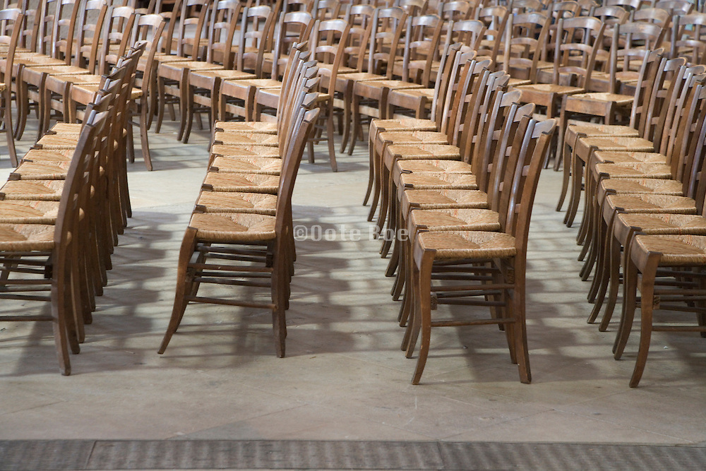 rows of old style wooden chairs in church St. Eustache France Paris