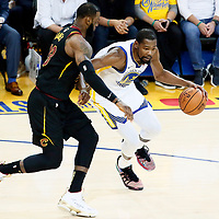 OAKLAND, CA - MAY 31: Kevin Durant #35 of the Golden State Warriors drives past LeBron James #23 of the Cleveland Cavaliers in Game One of the 2018 NBA Finals won 124-114 in OT by the Golden State Warriors over the Cleveland Cavaliers at the Oracle Arena on May 31, 2018 in Oakland, California. NOTE TO USER: User expressly acknowledges and agrees that, by downloading and or using this photograph, User is consenting to the terms and conditions of the Getty Images License Agreement. Mandatory Copyright Notice: Copyright 2018 NBAE (Photo by Chris Elise/NBAE via Getty Images)